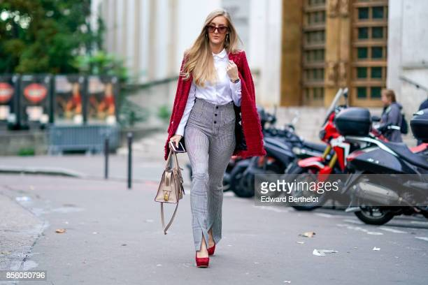 Leslie Huhn wears a red jacket a white shirt black and white striped pants red shoes outside Rahul Mishra during Paris Fashion Week Womenswear...