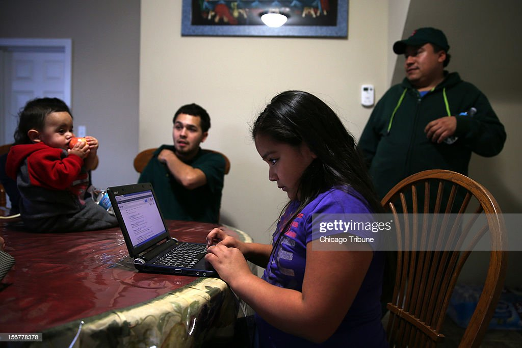 Leslie Mendoza uses a laptop as her father, Felipe, right, his nephew Aaron Carillo and Carillo's son, Jayden, talk in the home htey rent in Aurora, Illinois, on November 13, 2012. Some are turning foreclosed homes into investments by buying and turning them into rental properties.