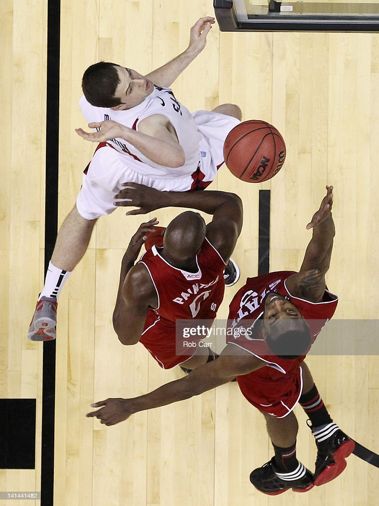 J Leslie of the North Carolina State Wolfpack and teammate DeShawn Painter fight for a rebound with Patrick Johnson San Diego State Aztecs during the...