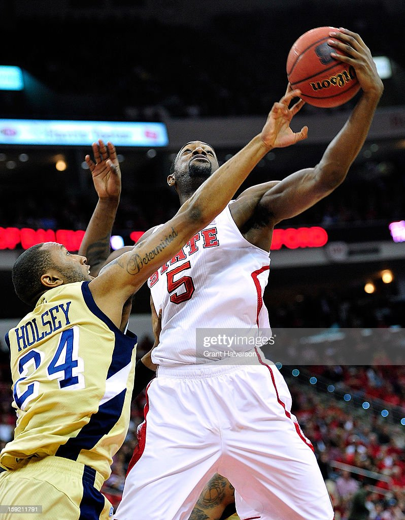 C.J. Leslie #5 of the North Carolina State Wolfpack battles for a rebound against Kammeon Holsey #24 of the Georgia Tech Yellow Jackets during play at PNC Arena on January 9, 2013 in Raleigh, North Carolina.