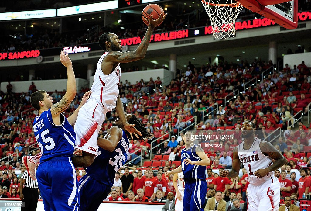 C.J. Leslie #5 of the North Carolina State Wolfpack draws a blocking foul against Jon Nwannunu #35 of the North Carolina-Asheville Bulldogs during play at PNC Arena on November 23, 2012 in Raleigh, North Carolina. North Carolina State won 82-80.