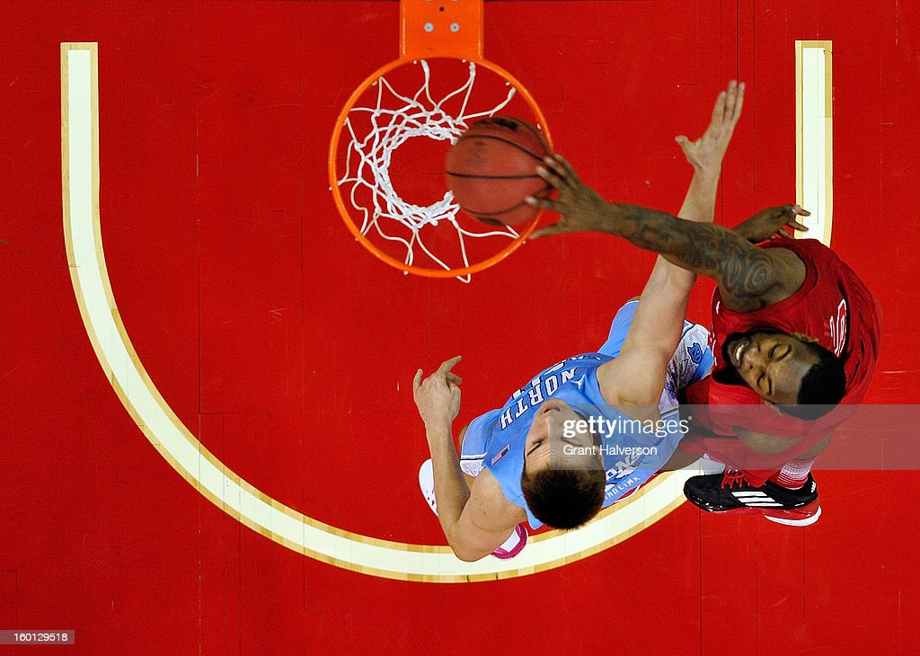 C.J. Leslie #5 of the North Carolina State Wolfpack dunks over Jackson Simmons #21 of the North Carolina Tar Heels during play at PNC Arena on January 26, 2013 in Raleigh, North Carolina.