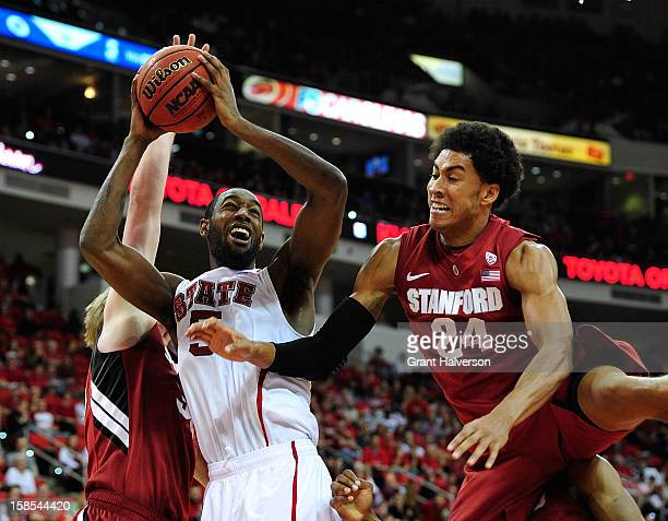 J Leslie of the North Carolina State Wolfpack pulls down a rebound against John Gage and Josh Huestis#24 of the Stanford Cardinal during play at PNC...