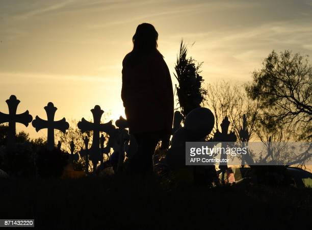 Leslie Vandevier prays at a memorial of crosses after a mass shooting that killed 26 people in Sutherland Springs Texas on November 7 2017 A gunman...