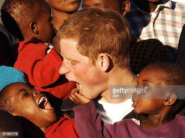 Britain's Prince Harry plays with children Mutsu and Lintle in the grounds of the Mants'ase children's home 24 April 2006 while on a return visit to...