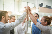 Shot of a team of colleagues celebrating with a high five in a modern office