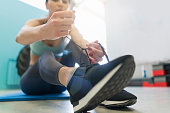 Beautiful, young female athlete tying her shoelace and preparing for a training session in the gym.