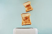 """Studio shot of toast popping out of a toaster with the words """"wake up"""" on them against a turquoise background"""