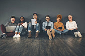 Studio shot of a diverse group of creative employees social networking against a grey background