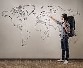 A young Asian guy with black glasses planning his next adventures on the map drawn on the wall, he is ready to go with his huge backpack already on his back.