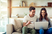 Shot of a happy young couple making a credit card payment on a laptop together at home