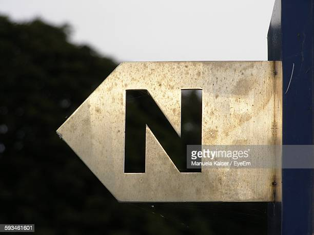 Letter N On Directional Sign Against Clear Sky