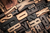 Random letterpress block letters stacked together with studio lighting forming a useful background