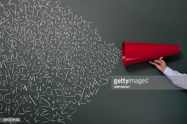 Letras y números salen de megáfono en pizarra rojo
