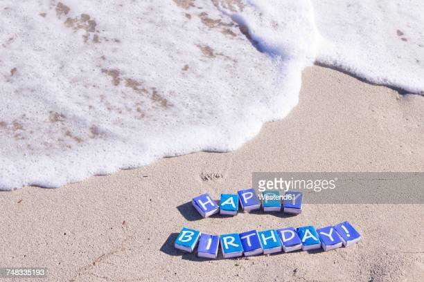 Letters on match boxes building the word Happy Birthday on the beach