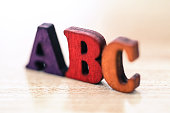 ABC letters isolated over table background with reflection.