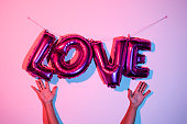 the hands of a young man and some fuchsia letter-shaped balloons forming the word love hanging on a pink wall, with a stroboscopic effect