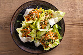 Lettuce wraps with chicken, carrot, peanuts and scallion. Stuffed iceberg lettuce leaves with chicken. View from above, top