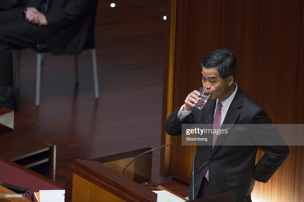 Leung Chun-ying, Hong Kong's chief executive, drinks from a glass of water while speaking in the chamber of the Legislative Council in Hong Kong, China, on Wednesday, Jan. 16, 2013. Hong Kong will maintain property curbs for overseas buyers as it seeks to meet the housing needs of its people, Leung said in his first policy address today. Photographer: Jerome Favre/Bloomberg via Getty Images