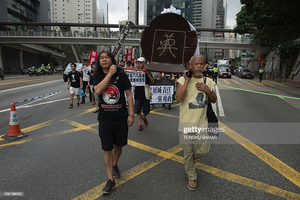 Leung Kwok-hung (L), also known as Long Hair, marches with a symbolic coffin representing the death of democracy during a pro-democracy rally ahead of the anniversary of the June 4, 1989 Tiananmen Square crackdown, in Hong Kong on May 29, 2016. People will gather in Hong Kong on June 4 for the annual remembrance ceremony to mark the 27th anniversary of the Tiananmen Square crackdown. / AFP / TENGKU