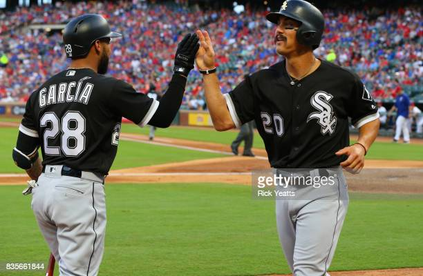 Leury Garcia of the Chicago White Sox congratulates Tyler Saladino for scoring in the first inning against the Texas Rangers at Globe Life Park in...