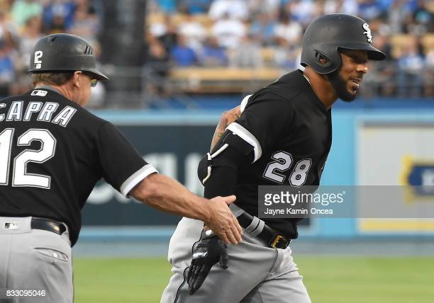 Leury Garcia of the Chicago White Sox is greeted by third base coach Nick Capra of the Chicago White Sox as he rounds third on a solo home run off...