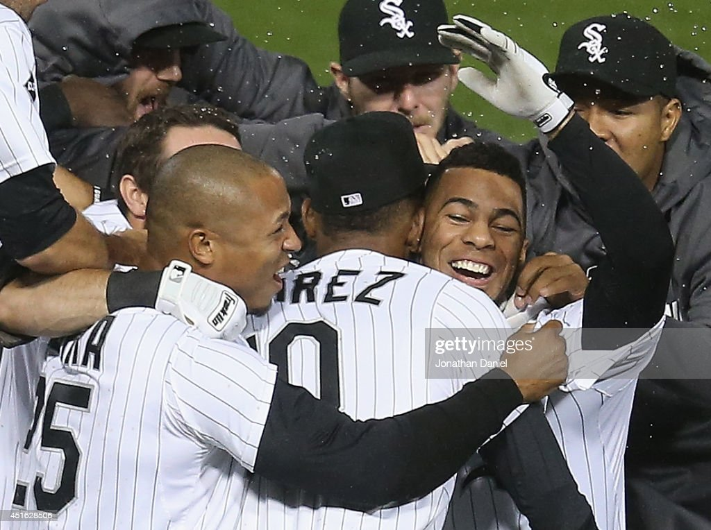 Leury Garcia #28 of the Chicago White Sox (R, arm in air) is mobbed by teammates including Alexei Ramirez #10 and Moises Sierra #25 after hitting a game-winning, walk-off single in the 9th inning against the Los Angeles Angels of Anaheim at U.S. Cellular Field on July 2, 2014 in Chicago, Illinois. The White Sox defeated the Angels 3-2.