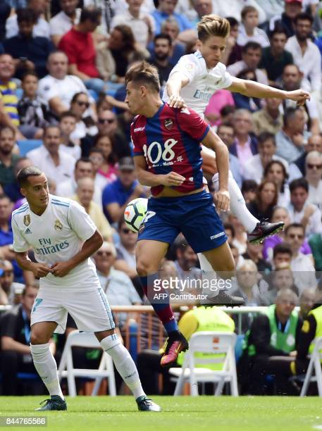 Levante's forward Alex Alegria vies with Real Madrid's miedfieder Marcos Llorente beside Real Madrid's midfielder Lucas Vazquez during the Spanish...