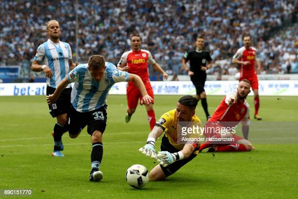 Levent Aycicek of 1860 Muenchen and Philipp Pentke goaltender of Jahn Regensburg compete for the ball during the Second Bundesliga Playoff second leg...