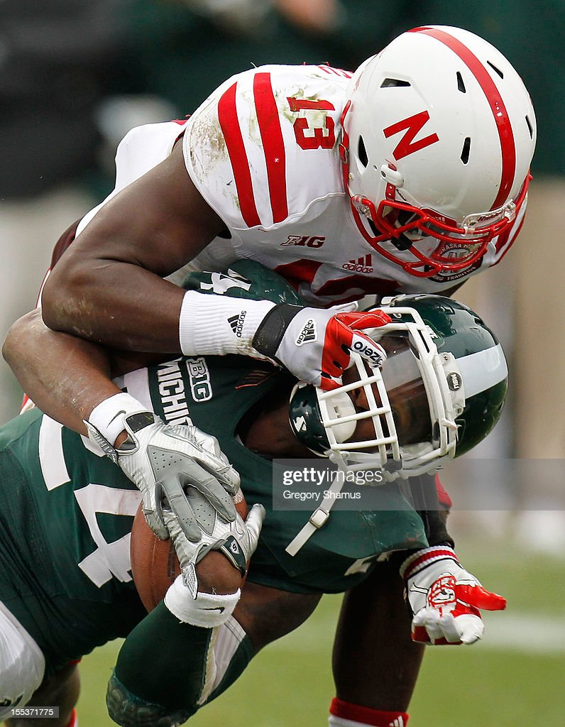 Le'Veon Bell #24 of the Michigan State Spartans battles for extra yards during a second quarter run while being tackled by P.J. Smith #13 of the Nebraska Cornhuskers at Spartan Stadium Stadium on November 3, 2012 in East Lansing, Michigan.