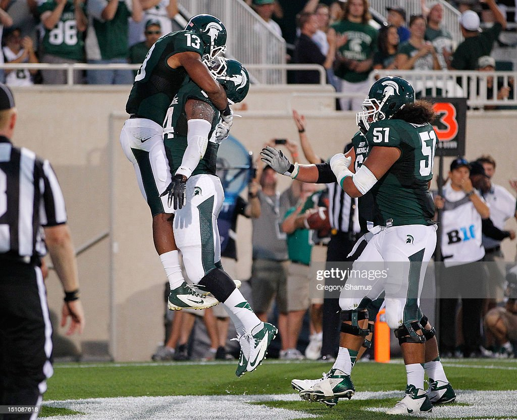 Le'Veon Bell #24 of the Michigan State Spartans celebrates a first-quarter touchdown with teammates Bennie Fowler #13 and Fou Fonoti #51 while playing the Boise State Broncos at Spartan Stadium on August, 2010 in East Lansing, Michigan.