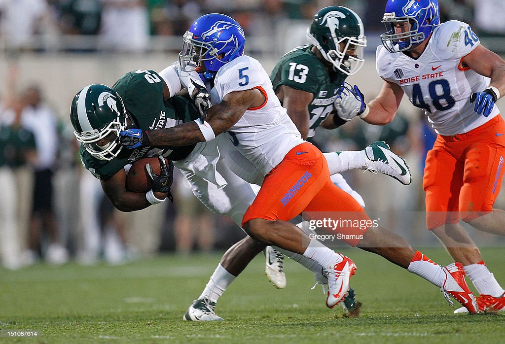 Le'Veon Bell #24 of the Michigan State Spartans is tackeled by Jamar Taylor #5 of the Boise State Broncos during a first-quarter run at Spartan Stadium on August, 2010 in East Lansing, Michigan.