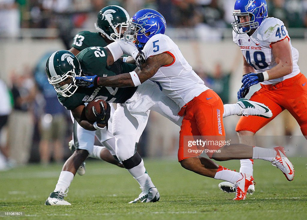 Le'Veon Bell #24 of the Michigan State Spartans is tackled by Jamar Taylor #5 of the Boise State Broncos during a first-quarter run at Spartan Stadium on August, 2010 in East Lansing, Michigan.