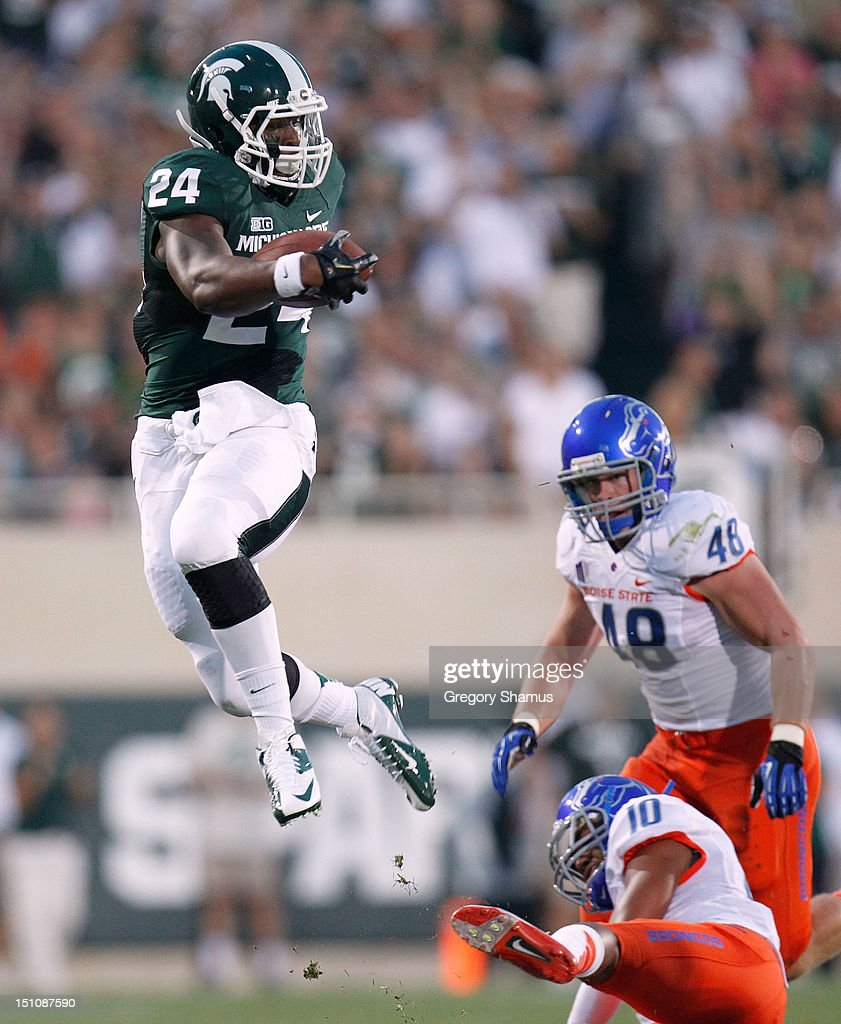 Le'Veon Bell #24 of the Michigan State Spartans jumps over the attempted tackle of Jeremy Ioane #10 of the Boise State Broncos at Spartan Stadium on August, 2010 in East Lansing, Michigan.