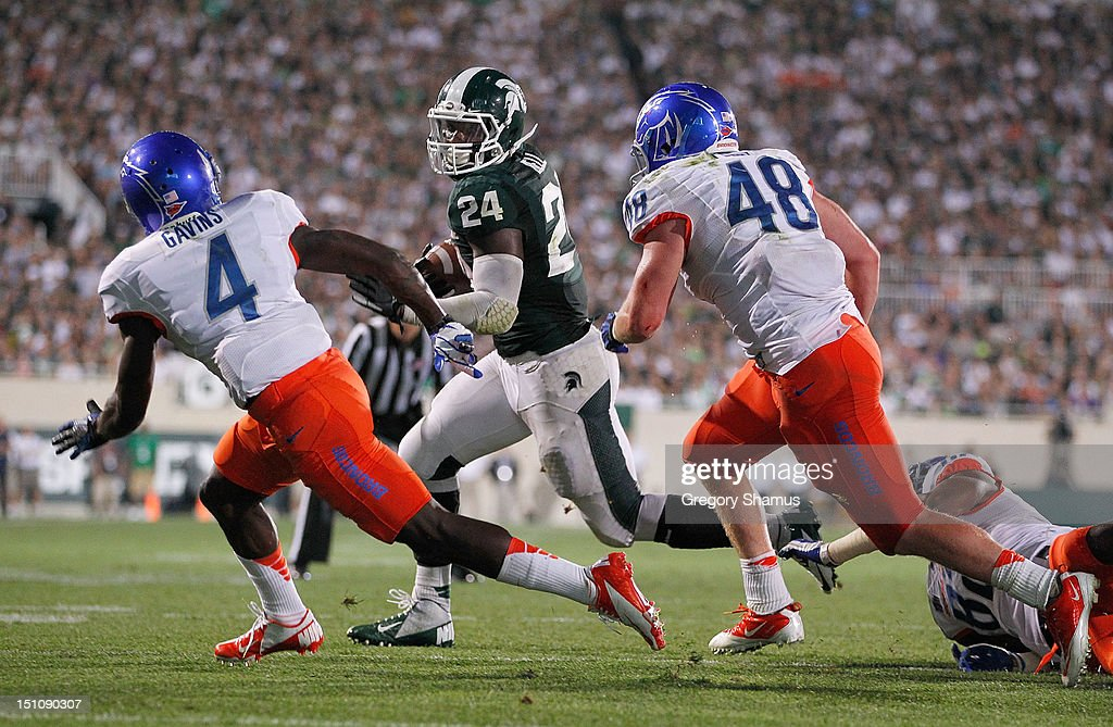 Le'Veon Bell #24 of the Michigan State Spartans runs for a fourth quarter touchdown while being chased by Jerrell Gavins #4 and J.C. Percy #48 of the Boise State Broncos at Spartan Stadium on August, 2010 in East Lansing, Michigan. Michigan State won the game 17-13.