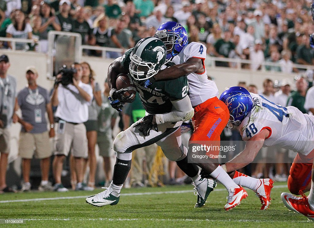 Le'Veon Bell #24 of the Michigan State Spartans runs for a fourth quarter touchdown while being tackled by Jerrell Gavins #4 and J.C. Percy #48 of the Boise State Broncos at Spartan Stadium on August, 2010 in East Lansing, Michigan. Michigan State won the game 17-13.