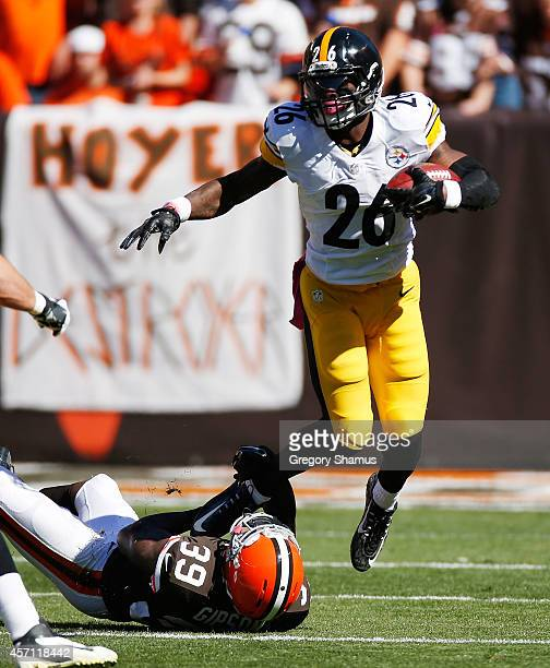 Le'Veon Bell of the Pittsburgh Steelers avoids a tackle by Tashaun Gipson of the Cleveland Browns during the first quarter at FirstEnergy Stadium on...