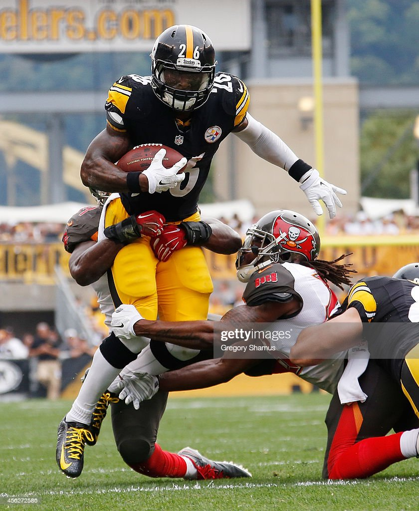 Le'Veon Bell #26 of the Pittsburgh Steelers gets dragged down by Jacquies Smith #56 and Mark Barron #23 of the Tampa Bay Buccaneers during the first quarter at Heinz Field on September 28, 2014 in Pittsburgh, Pennsylvania.