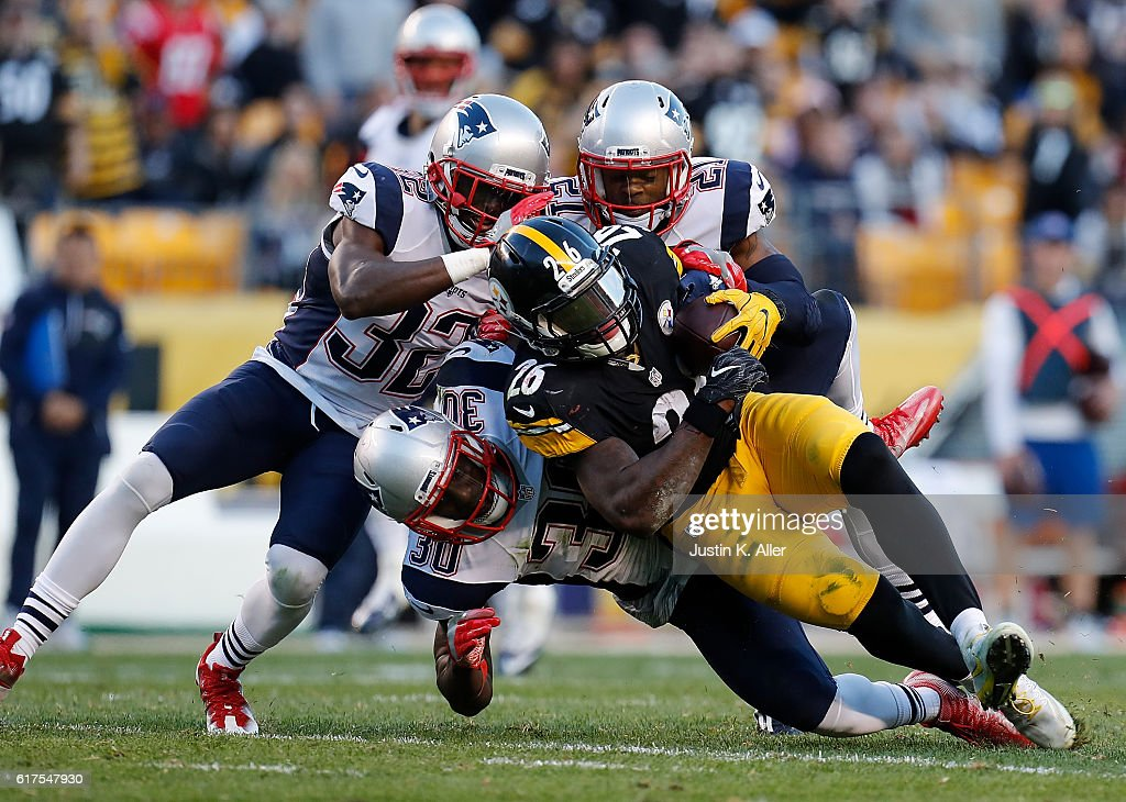 Le'Veon Bell #26 of the Pittsburgh Steelers is tackled by Devin McCourty #32, Duron Harmon #30 and Malcolm Butler #21 of the New England Patriots in the first half during the game at Heinz Field on October 23, 2016 in Pittsburgh, Pennsylvania.