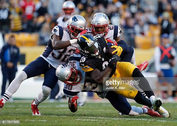 Le'Veon Bell of the Pittsburgh Steelers is tackled by Devin McCourty Duron Harmon and Malcolm Butler of the New England Patriots in the first half...