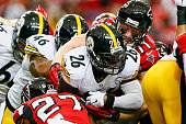 Le'Veon Bell of the Pittsburgh Steelers is tackled by Robert McClain and Kroy Biermann of the Atlanta Falcons in the first half at the Georgia Dome...