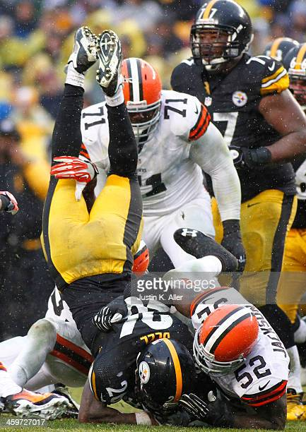 Le'Veon Bell of the Pittsburgh Steelers is up ended while rushing against the Cleveland Browns during the game on December 29 2013 at Heinz Field in...