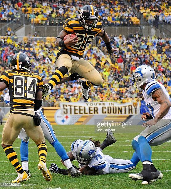 Le'Veon Bell of the Pittsburgh Steelers jumps to avoid a tackle by Willie Young of the Detroit Lions on November 17 2013 at Heinz Field in Pittsburgh...