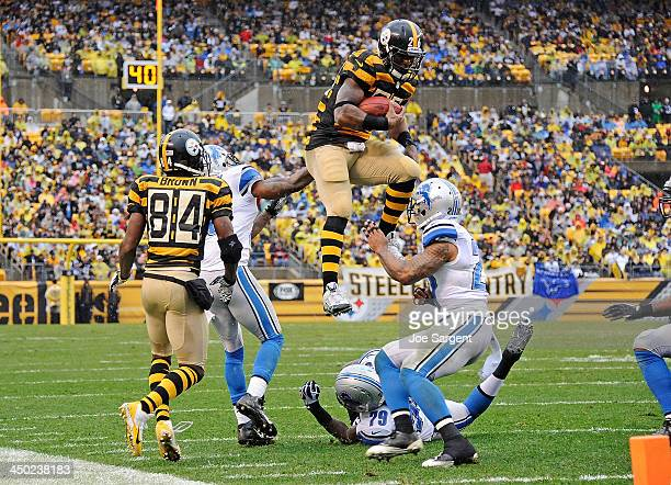 Le'Veon Bell of the Pittsburgh Steelers jumps to avoid a tackle by Willie Young of the Detroit Lions in front of Glover Quin on November 17 2013 at...