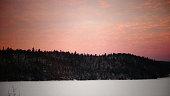 Ciel rosé par le lever du jour sur la montagne près de la rivière recouverte de neige