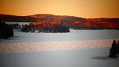 Ciel orangé au lever du soleil sur une étendue d'eau recouverte de neige