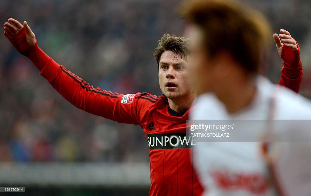 Leverkusen's defender Sebastian Boenisch (L) reacts during the German first division Bundesliga football match Bayer Leverkusen vs FC Augsburg in Leverkusen, western Germany, on February 16, 2013. Leverkusen won the match 2-1. AFP PHOTO / PATRIK STOLLARZ