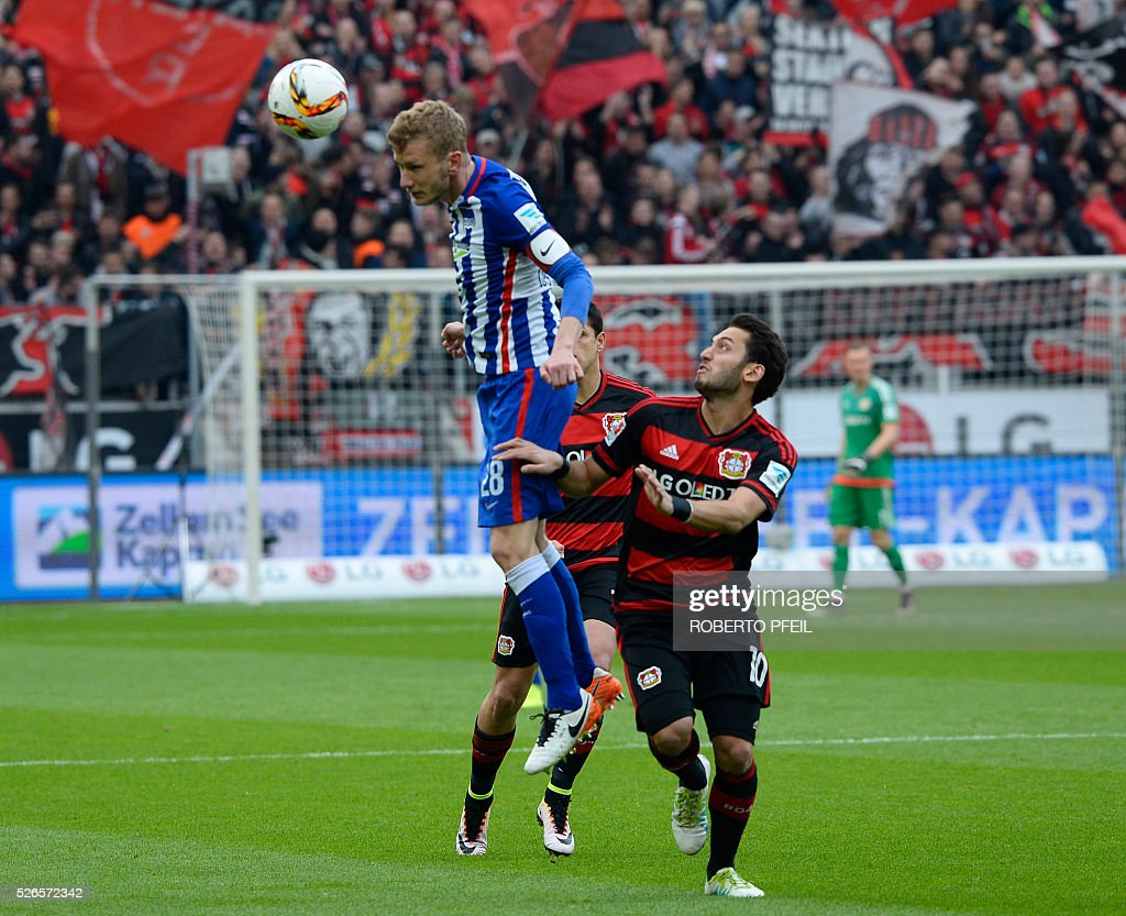 Leverkusen`s Hakan Calhanoglu (R) and Berlin's Fabian Lusteberger (l) vie for the ball during the German first division Bundesliga football match Bayer 04 Leverkusen v Hertha Berlin in Leverkusen, western Germany, on April 30, 2016. / AFP / Roberto Pfeil