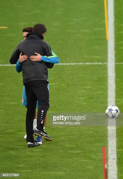 Leverkusen's head coach Roger Schmidt hugs Leverkusen's midfielder Hakan Calhanoglu during a training session in Leverkusen on February 20 2017 on...