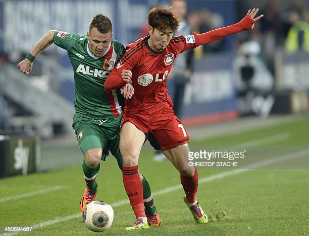 Leverkusen's Korean striker HeungMin Son and Augsburg's defender Ronny Philp vie for the ball during the German first division Bundesliga football...